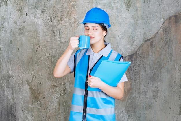 Vrouwelijke ingenieur in blauw uniform en helm die een blauwe theekop en een blauwe rapportmap vasthoudt en het product ruikt