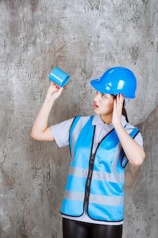 Vrouwelijke ingenieur in blauw uniform en helm die een blauwe theekop ondersteboven houdt en van streek raakt
