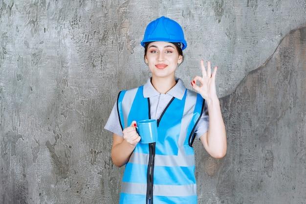 Vrouwelijke ingenieur in blauw uniform en helm die een blauwe theekop vasthoudt en een teken van plezier toont.