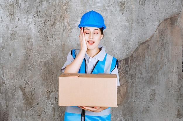 Vrouwelijke ingenieur in blauw uniform en helm die een kartonnen pakket vasthoudt en de hand op haar gezicht legt terwijl ze verrast is.
