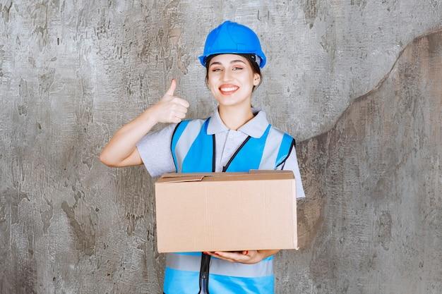 Vrouwelijke ingenieur in blauw uniform en helm die een kartonnen pakket vasthoudt en een positief handteken toont