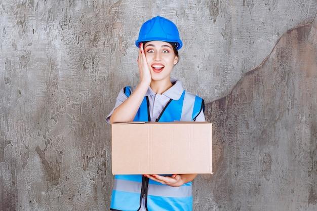 Vrouwelijke ingenieur in blauw uniform en helm die een kartonnen pakket vasthoudt en haar hand op haar gezicht legt terwijl ze verrast is
