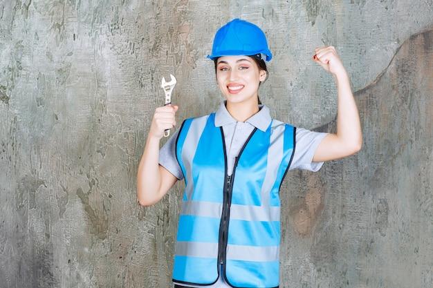 Vrouwelijke ingenieur in blauw uniform en helm die een metalen moersleutel vasthoudt en een positief handteken toont.