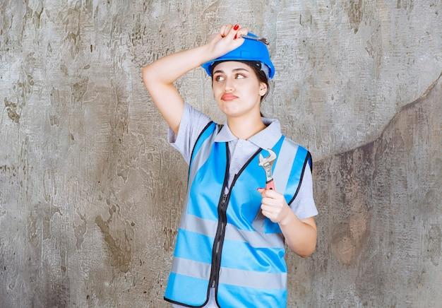 Vrouwelijke ingenieur in blauw uniform en helm die een metalen moersleutel vasthoudt en zich verward en bedachtzaam voelt over hoe het te gebruiken.