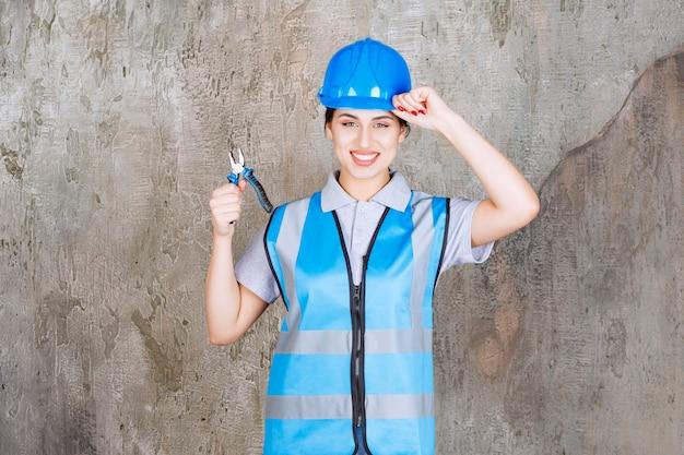 Vrouwelijke ingenieur in blauw uniform en helm die een metalen tang vasthoudt voor reparatie en een positief handteken toont.