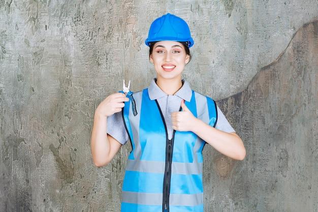 Vrouwelijke ingenieur in blauw uniform en helm die een metalen tang vasthoudt voor reparatie en een positief handteken toont
