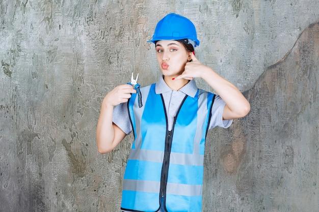 Vrouwelijke ingenieur in blauw uniform en helm die een metalen tang vasthoudt voor reparatie en om een telefoontje vraagt