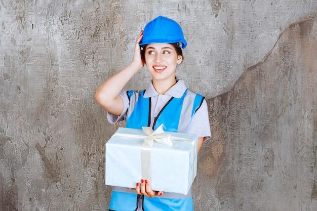 Vrouwelijke ingenieur in blauw uniform en helm met een blauwe geschenkdoos en ziet er verrast en opgewonden uit