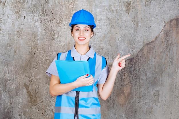 Vrouwelijke ingenieur in blauw uniform en helm met een blauwe rapportmap en wijzend op iemand rond.