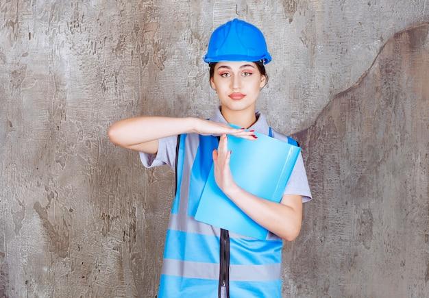 Vrouwelijke ingenieur in blauw uniform en helm met een blauwe rapportmap