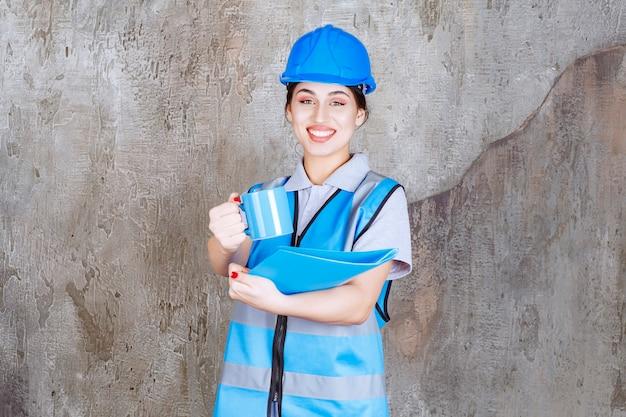 Vrouwelijke ingenieur in blauw uniform en helm met een blauwe theekop en een blauwe rapportmap en het drankje aanbieden aan haar collega.