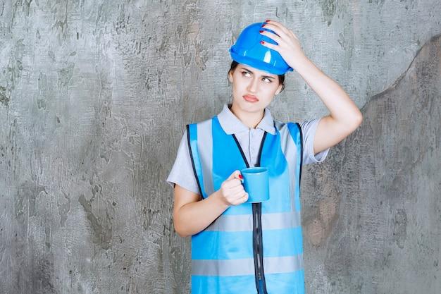 Vrouwelijke ingenieur in blauw uniform en helm met een blauwe theekop en ziet er verward en gestrest uit.
