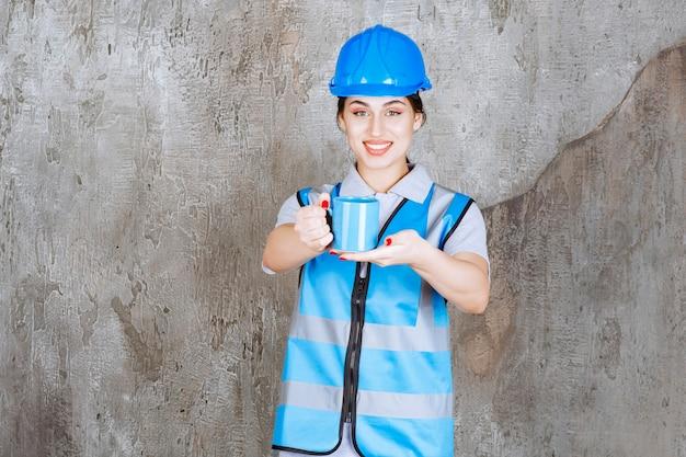 Vrouwelijke ingenieur in blauw uniform en helm met een blauwe theekop.