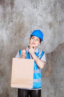 Vrouwelijke ingenieur in blauw uniform en helm met een boodschappentas en ziet er attent uit