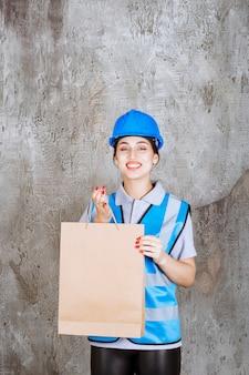 Vrouwelijke ingenieur in blauw uniform en helm met een boodschappentas en ziet er verrast uit.