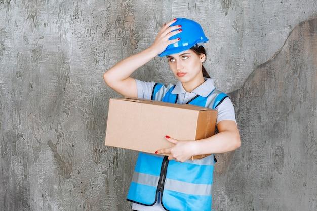 Vrouwelijke ingenieur in blauw uniform en helm met een kartonnen pakket en ziet er moe en ontevreden uit.