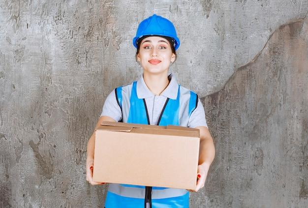 Vrouwelijke ingenieur in blauw uniform en helm met een kartonnen pakket.
