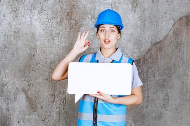 Vrouwelijke ingenieur in blauw uniform en helm met een leeg rechthoekig infobord en een teken van plezier.