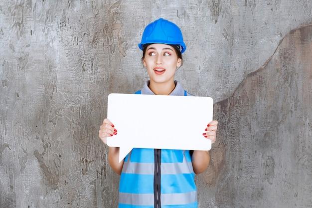 Vrouwelijke ingenieur in blauw uniform en helm met een leeg rechthoekig infobord en ziet er verward en doodsbang uit.