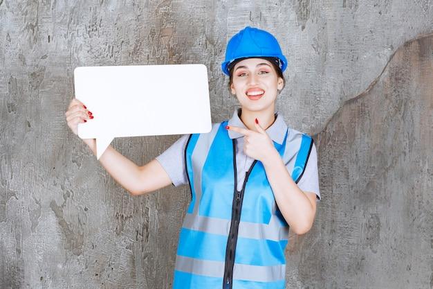 Vrouwelijke ingenieur in blauw uniform en helm met een leeg rechthoekig infobord