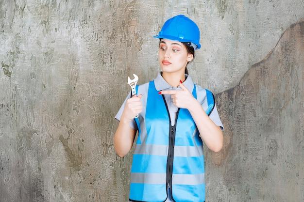 Vrouwelijke ingenieur in blauw uniform en helm met een metalen moersleutel.