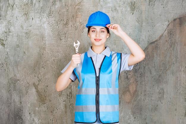 Vrouwelijke ingenieur in blauw uniform en helm met een metalen moersleutel. Premium Foto