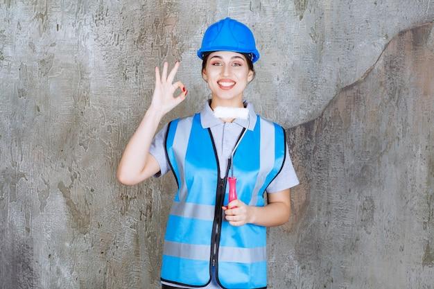 Vrouwelijke ingenieur in blauw uniform en helm met een trimrol om te schilderen en een positief handteken te tonen