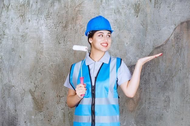 Vrouwelijke ingenieur in blauw uniform en helm met een trimrol om te schilderen en naar de betonnen muur erachter te wijzen.