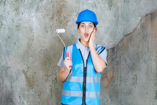 Vrouwelijke ingenieur in blauw uniform en helm met een trimrol om te schilderen en ziet er bang en doodsbang uit.