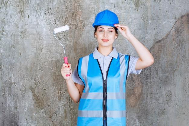 Vrouwelijke ingenieur in blauw uniform en helm met een trimrol om te schilderen.