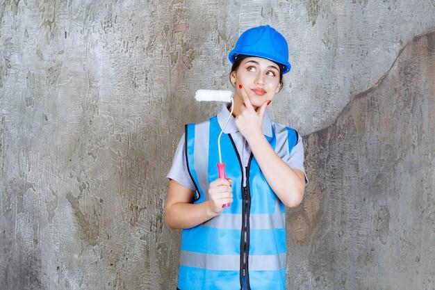 Vrouwelijke ingenieur in blauw uniform en helm met een trimrol voor schilderen en denken en plannen.