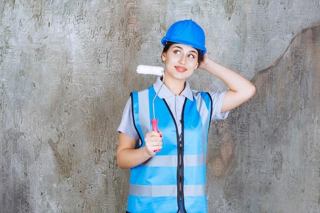 Vrouwelijke ingenieur in blauw uniform en helm met een trimroller voor schilderen en denken en plannen.