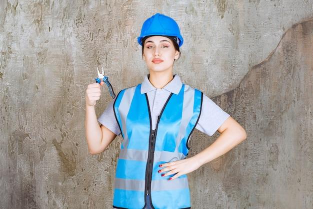 Vrouwelijke ingenieur in blauw uniform en helm met metalen tang voor reparatie