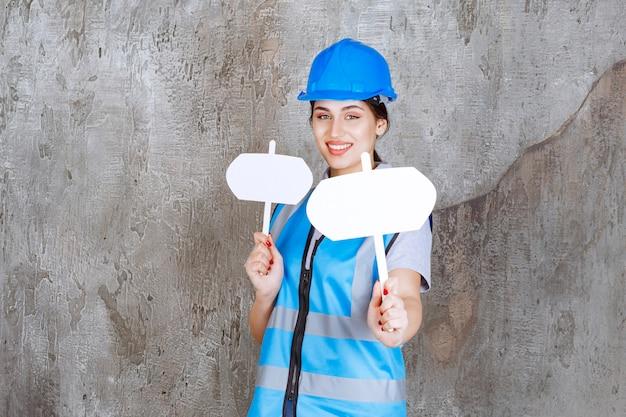 Vrouwelijke ingenieur in blauw uniform en helm met twee lege infoborden in beide handen.