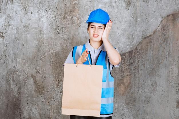 Vrouwelijke ingenieur in blauwe helm en uitrusting met een kartonnen boodschappentas, hoofd vast en ziet er moe uit