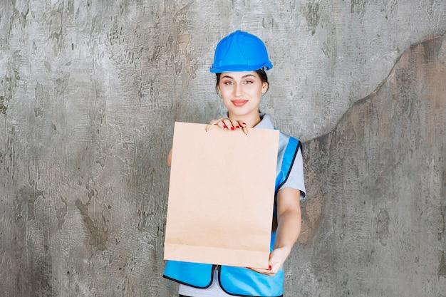 Vrouwelijke ingenieur in blauwe helm en uitrusting met een kartonnen boodschappentas.