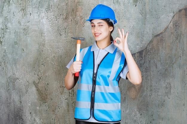 Vrouwelijke ingenieur in blauwe uitrusting en helm die een bijl met houten handvat houdt en positief handteken toont.