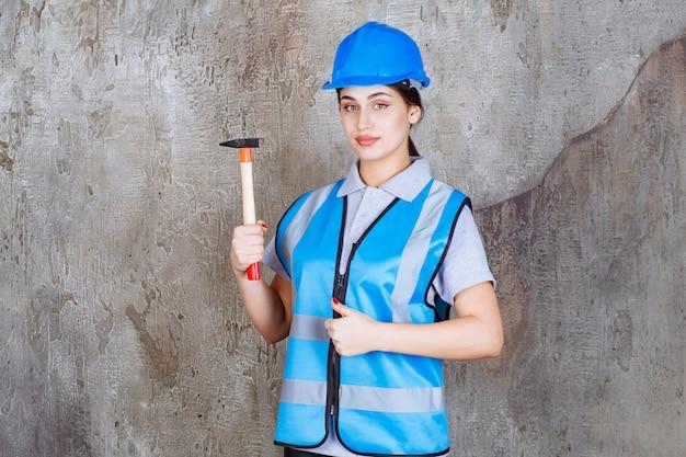 Vrouwelijke ingenieur in blauwe uitrusting en helm die een bijl met houten handvat houdt en positief handteken toont