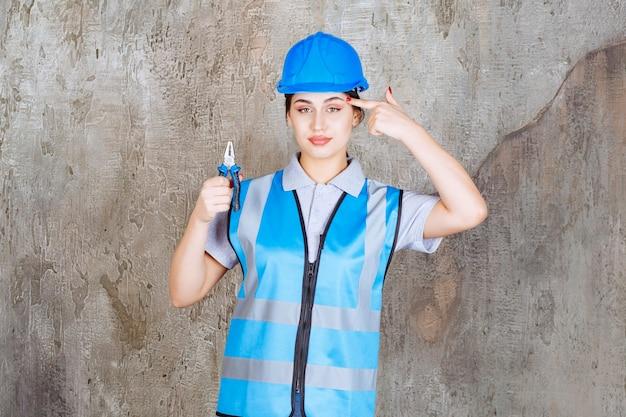 Vrouwelijke ingenieur in blauwe uitrusting en helm die een tang vasthoudt voor reparatiewerkzaamheden en een idee heeft