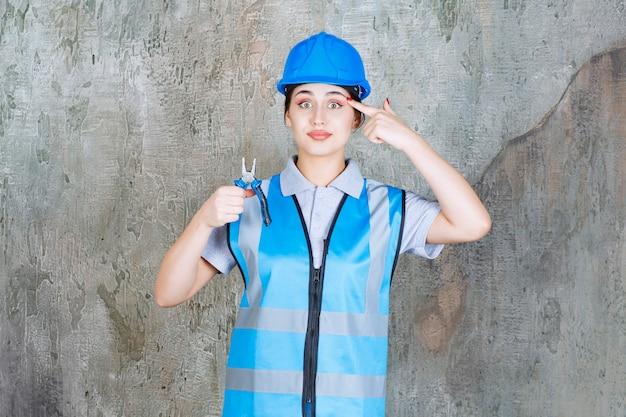 Vrouwelijke ingenieur in blauwe uitrusting en helm die een tang vasthoudt voor reparatiewerkzaamheden en een idee heeft.
