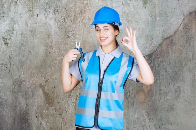 Vrouwelijke ingenieur in blauwe uitrusting en helm die een tang vasthoudt voor reparatiewerkzaamheden en een positief handteken toont.