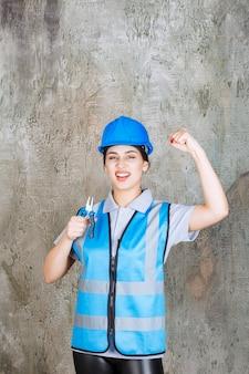 Vrouwelijke ingenieur in blauwe uitrusting en helm die een tang vasthoudt voor reparatiewerkzaamheden en haar vuist laat zien.