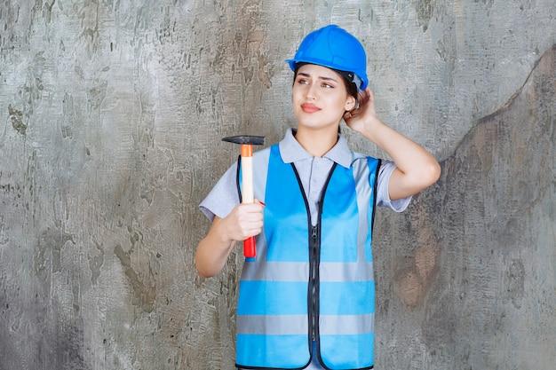 Vrouwelijke ingenieur in blauwe uitrusting en helm met een bijl met houten handvat en ziet er attent uit