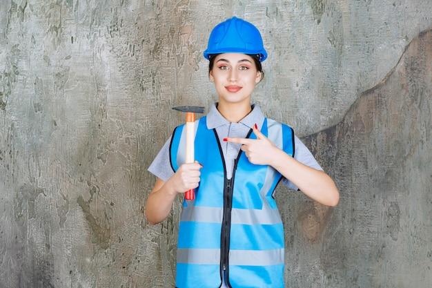 Vrouwelijke ingenieur in blauwe versnelling en helm met een bijl met houten handvat.