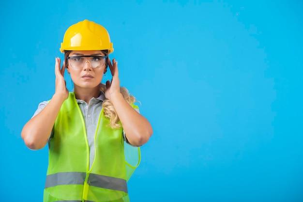 Vrouwelijke ingenieur in gele helm en uitrusting die preventieve oogglazen draagt.