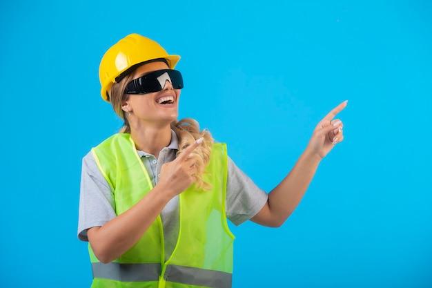 Vrouwelijke ingenieur in gele helm en uitrusting die preventieve oogglazen van stralen dragen.