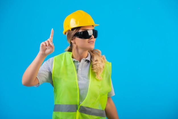 Vrouwelijke ingenieur in gele helm en uitrusting die preventieve oogglazen van stralen dragen