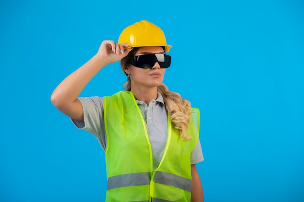 Vrouwelijke ingenieur in gele helm en uitrusting die preventieve straalbrillen draagt en zich zelfverzekerd voelt.