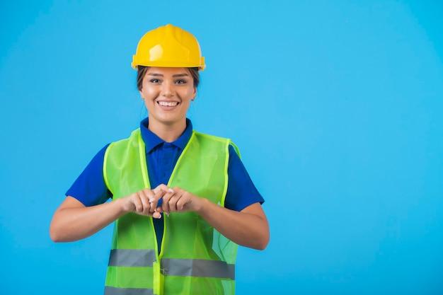 Vrouwelijke ingenieur in gele helm en uitrusting die zich zelfverzekerd voelt