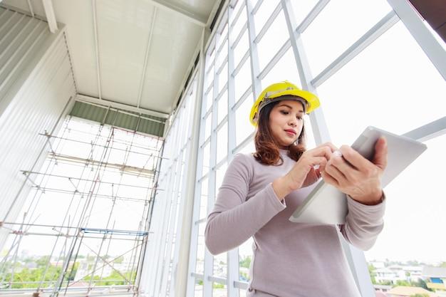 Vrouwelijke ingenieur in gele veiligheidshelm kijkt naar tabletcomputer